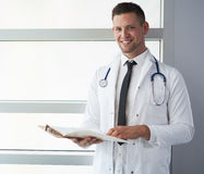 Портрет мужского доктора держа его терпеливую диаграмму в яркой современной больнице Стоковые Фото