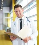 Портрет мужского доктора держа его терпеливую диаграмму в яркой современной больнице Стоковые Фотографии RF