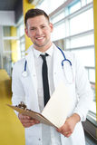 Портрет мужского доктора держа его терпеливую диаграмму в яркой современной больнице Стоковые Изображения