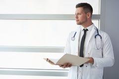Портрет мужского доктора держа его терпеливую диаграмму в яркой современной больнице Стоковое Фото