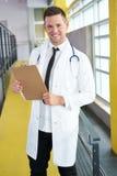 Портрет мужского доктора держа его терпеливую диаграмму в яркой современной больнице Стоковое фото RF