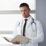 Портрет мужского доктора держа его терпеливую диаграмму в яркой современной больнице Стоковая Фотография RF