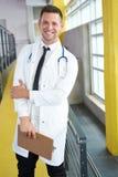 Портрет мужского доктора держа его терпеливую диаграмму в яркой современной больнице Стоковые Изображения RF