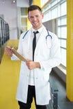 Портрет мужского доктора держа его терпеливую диаграмму в яркой современной больнице Стоковое Изображение