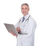 Портрет мужского доктора используя компьтер-книжку Стоковое фото RF