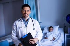 Портрет мужского доктора стоя с доской сзажимом для бумаги в палате Стоковое Фото