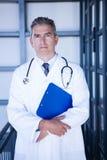Портрет мужского доктора стоя с доской сзажимом для бумаги Стоковое фото RF