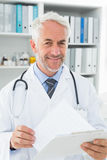 Портрет мужского доктора с отчетами в медицинском офисе Стоковая Фотография