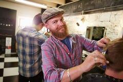 Портрет мужского парикмахера давая стрижку клиента в магазине Стоковые Изображения RF