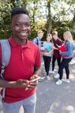 Портрет мужского подросткового Outdoors студента средней школы с Frien стоковое изображение