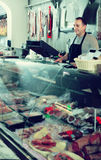 Портрет мужского продавца представляя с wursts в палачестве Стоковая Фотография RF