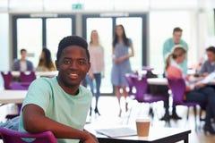 Портрет мужского студента колледжа ослабляя в столовой стоковое фото