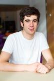 Портрет мужского студента колледжа сидя на столе Стоковое фото RF
