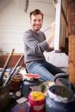 Портрет мужского художника работая на картине в студии стоковое изображение