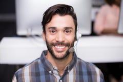 Портрет мужской исполнительной власти обслуживания клиента говоря на шлемофоне на столе Стоковые Изображения RF