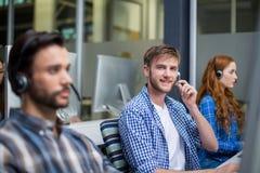 Портрет мужской исполнительной власти обслуживания клиента говоря на шлемофоне на столе Стоковая Фотография