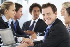 Портрет мужской исполнительной власти с встречей офиса в предпосылке Стоковые Фотографии RF