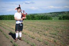 Портрет мужчины наслаждаясь играя пускает по трубам в килте Scotish традиционном на зеленом цвете outdoors Стоковые Фото