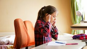 Портрет музыки девочка-подростка слушая с наушниками пока делающ домашнюю работу Стоковое фото RF