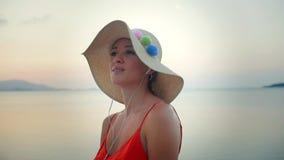 Портрет музыки молодой привлекательной девушки слушая с наушниками видеоматериал