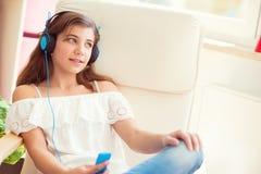 Портрет музыки молодого милого девочка-подростка слушая с moder Стоковая Фотография