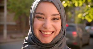 Портрет мусульманского студента в hijab усмехаясь жизнерадостно в положение камеры на зеленой улице города видеоматериал