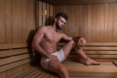 Портрет мышечного человека ослабляя в сауне стоковое изображение rf
