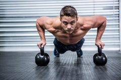 Портрет мышечный делать человека нажим-поднимает с kettlebells Стоковое Изображение