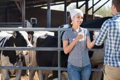 Портрет 2 наемных сельскохозяйственных рабочих держа стеклянными с молоком стоковое изображение