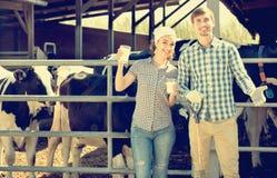 Портрет 2 наемных сельскохозяйственных рабочих держа стеклянными с молоком стоковое фото