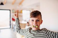 Портрет небольшого мальчика есть виноградины внутри помещения, имеющ потеху r стоковые фотографии rf