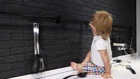 Портрет немного довольно босоногого ребёнка сидя на кухонном столе и играя с кухн-изделиями потеха отца ребенка имея играть совме видеоматериал