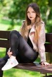 Портрет неофициальной модной девушки на стенде в парке Стоковые Изображения RF