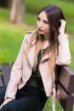 Портрет неофициальной модной девушки на стенде в парке Стоковое Изображение