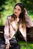 Портрет неофициальной модной девушки на стенде в парке Стоковая Фотография