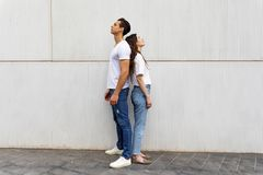 Портрет несчастного разочарованного положения пар спина к спине не говоря друг к другу после аргумента пока стоящ на сером цвете стоковые фото