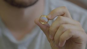 Портрет неузнаваемого бородатого человека держа золотое обручальное кольцо сидя дома Парень идя сделать предложение сток-видео