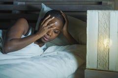 Портрет ночи образа жизни молодой унылой и усиленной черной Афро-американской женщины лежа на пробовать кровати расстроенный спат стоковые фотографии rf