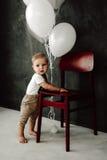 Портрет дня рождения 1 года симпатичного мальчика счастливого усмехаясь празднуя Один годовалый европейский мальчик сидя на поле Стоковое Изображение RF