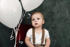 Портрет дня рождения 1 года симпатичного мальчика счастливого усмехаясь празднуя Один годовалый европейский мальчик сидя на поле Стоковые Изображения RF