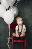 Портрет дня рождения 1 года симпатичного мальчика счастливого усмехаясь празднуя Один годовалый европейский мальчик сидя на поле Стоковые Фотографии RF