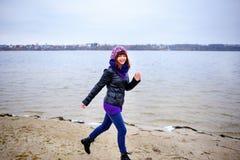 Портрет образа жизни женщины молодого кавказца тонкой бежит вдоль осени пляжа Стоковая Фотография