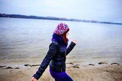 Портрет образа жизни женщины молодого кавказца тонкой бежит вдоль осени пляжа Стоковое Фото