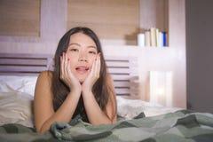 Портрет образа жизни молодой красивой и счастливой азиатской китайской женщины лежа в спальне кровати дома усмехаясь жизнерадостн стоковое фото rf