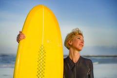 Портрет образа жизни молодой сексуальной красивой и счастливой женщины серфера держа желтое holid лета доски прибоя усмехаясь жиз стоковая фотография rf