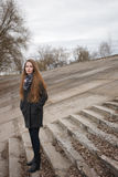 Портрет образа жизни молодой и милой взрослой женщины при шикарные длинные волосы представляя на конкретной лестнице в парке горо Стоковые Фотографии RF