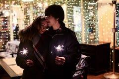 Портрет образа жизни пар в влюбленности держа сверкная фейерверки Нового Года на улицах города с серией светов на предпосылке Стоковые Фотографии RF