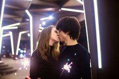 Портрет образа жизни пар в влюбленности держа сверкная фейерверки Нового Года на улицах города с серией светов на предпосылке Стоковое Фото