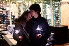 Портрет образа жизни пар в влюбленности держа сверкная фейерверки Нового Года на улицах города с серией светов на предпосылке Стоковые Фото