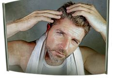 Портрет образа жизни привлекательного потревоженного и, который отнесенного кавказского человека смотря зеркало ванной комнаты на Стоковые Фотографии RF